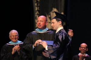 Mr. Pugh presents his son David with his diploma